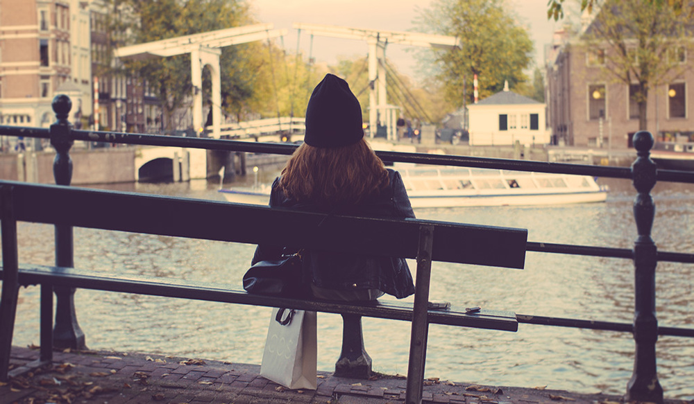 Chilled out girl in front of big Amstel river.