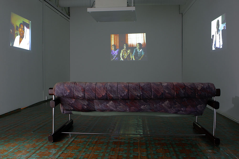 Two Rooms and a kitchen (2002),  Installation view: video projection, couch and a vinyl floor.