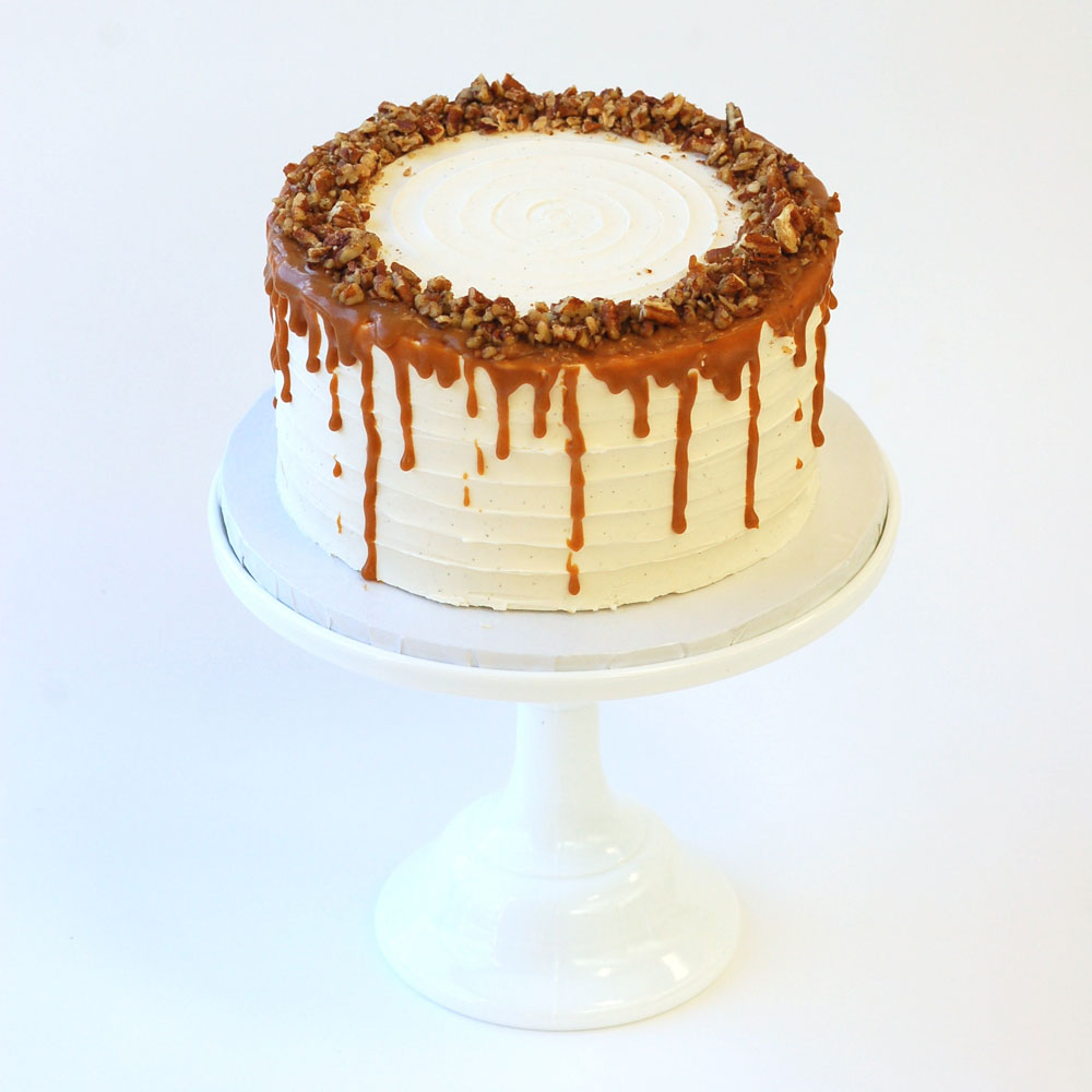 "Caramel Apple Cake (Specialty)   Cake :   Spiced Apple  Filling : Salted Caramel  Frosting : Vanilla-Bean Swiss Meringue Buttercream 6"" Round $50 8"" Round $75 10"" Round $110  Topped with caramel and walnuts."