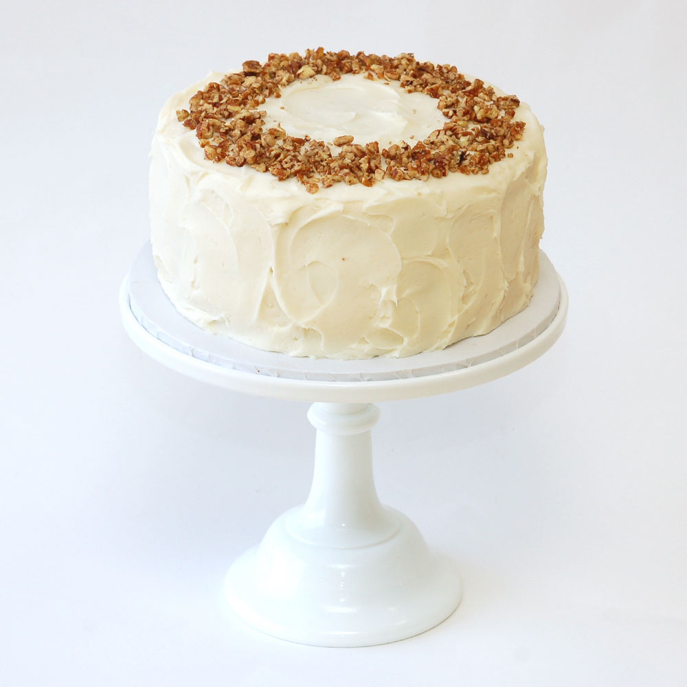 "Our Hummingbird Cake (Specialty)   Cake : Spiced Pineapple-Banana  Filling : No filling  Frosting : Cream Cheese Frosting 6"" Round $50 8"" Round $75 10"" Round $110  Topped with toasted pecans."