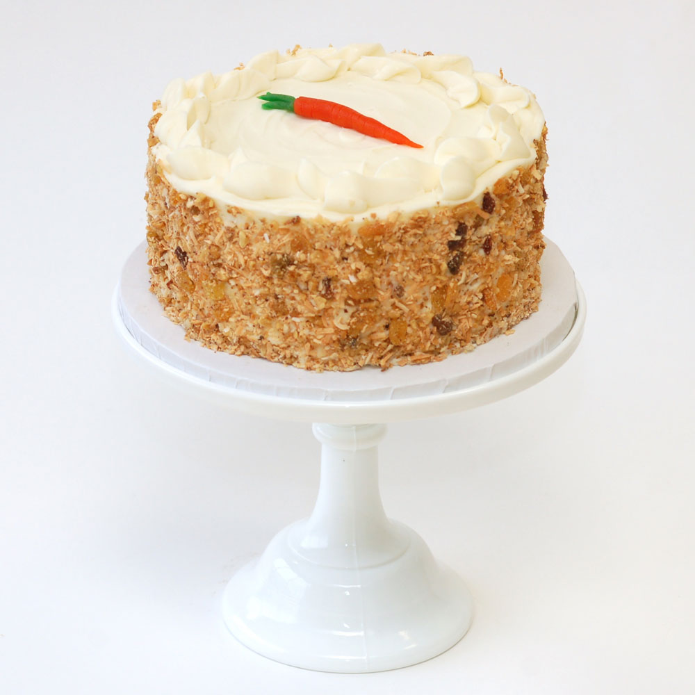 "The Ultimate Carrot Cake (Signature)   Cake : Carrot  Filling : No filling  Frosting : Regular or Chocolate Cream Cheese 6"" Round $40 8"" Round $60 10"" Round $90  Can be made vegan. Topped with a marzipan carrot - s  ides covered with toasted coconut, walnuts, and golden raisins."