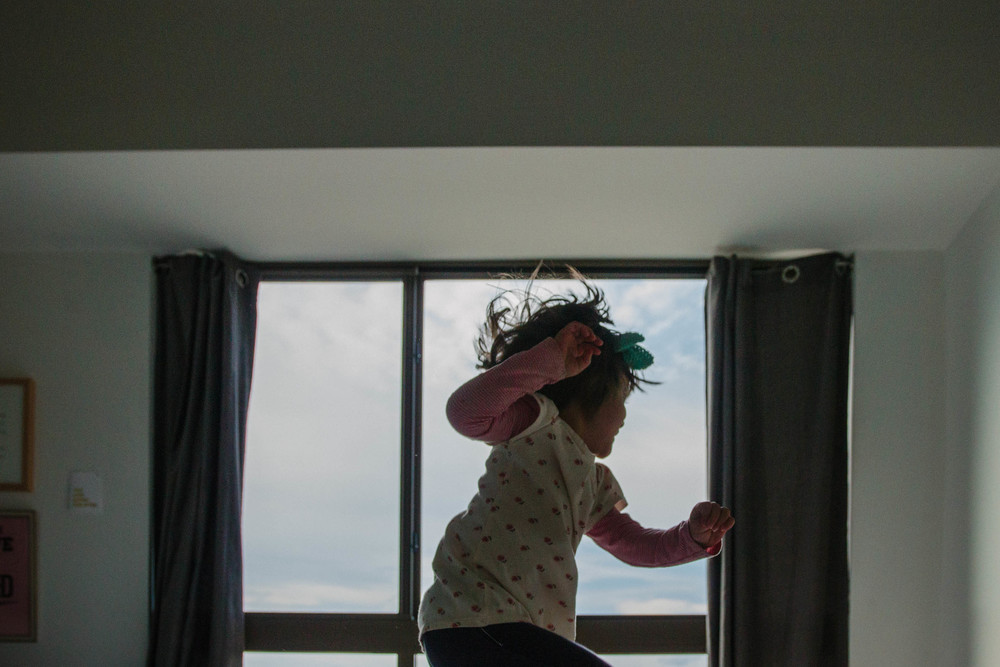Young girl jumps on the bed in front of a window