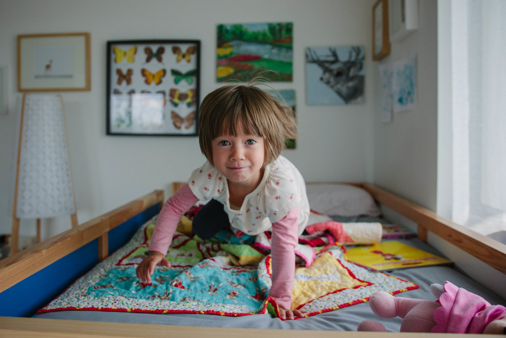 Young girl crawls on her bed in her room