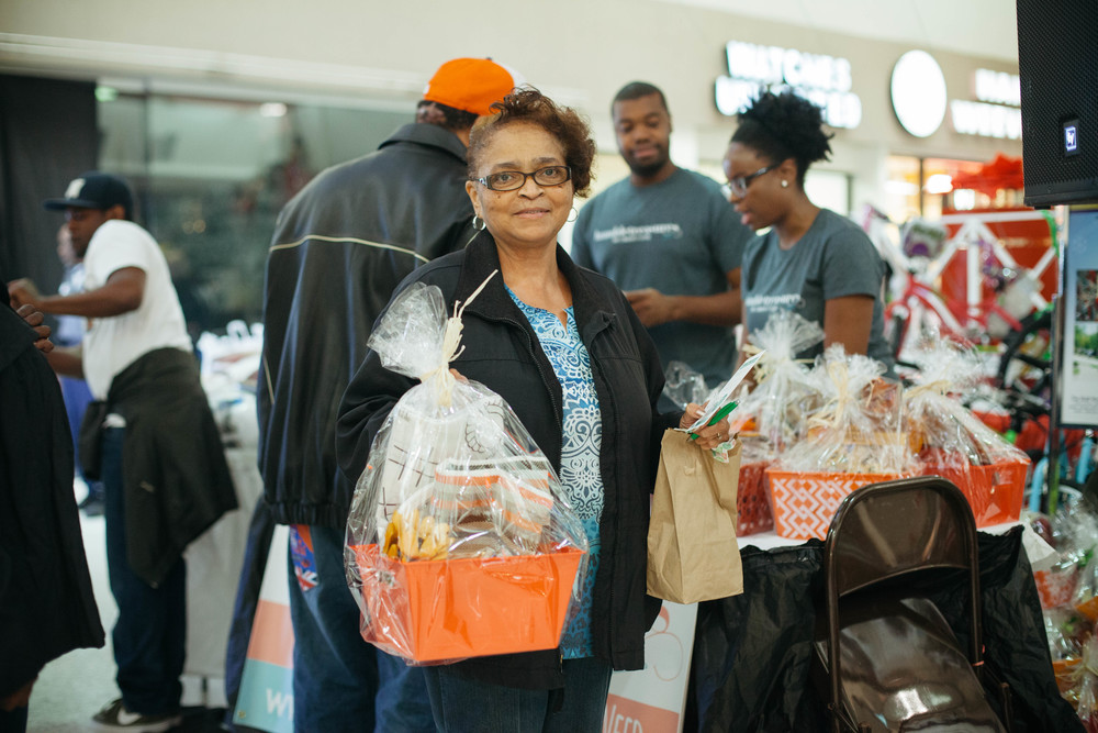 Woman receives basket at Thanksgiving Turkey Bash