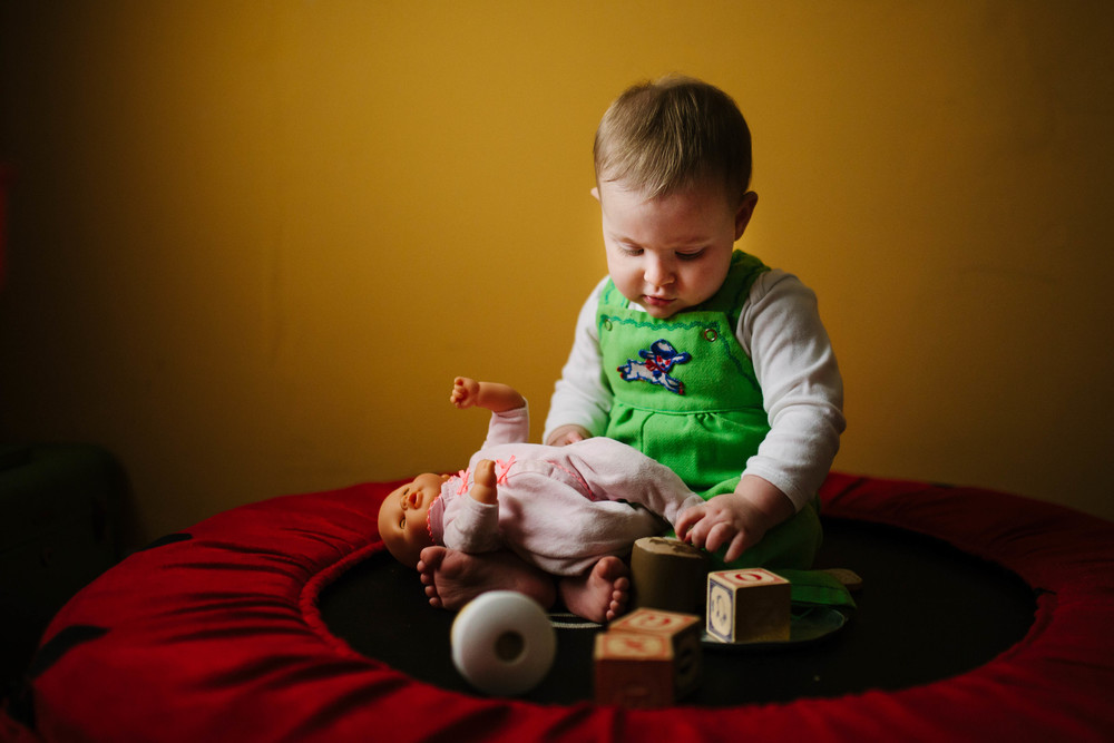 Portrait of Play image of infant playing with doll and blocks