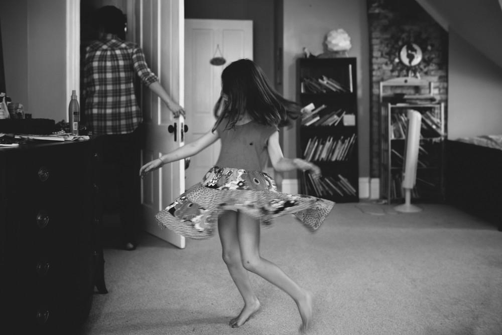 girl twirling in dress in attic
