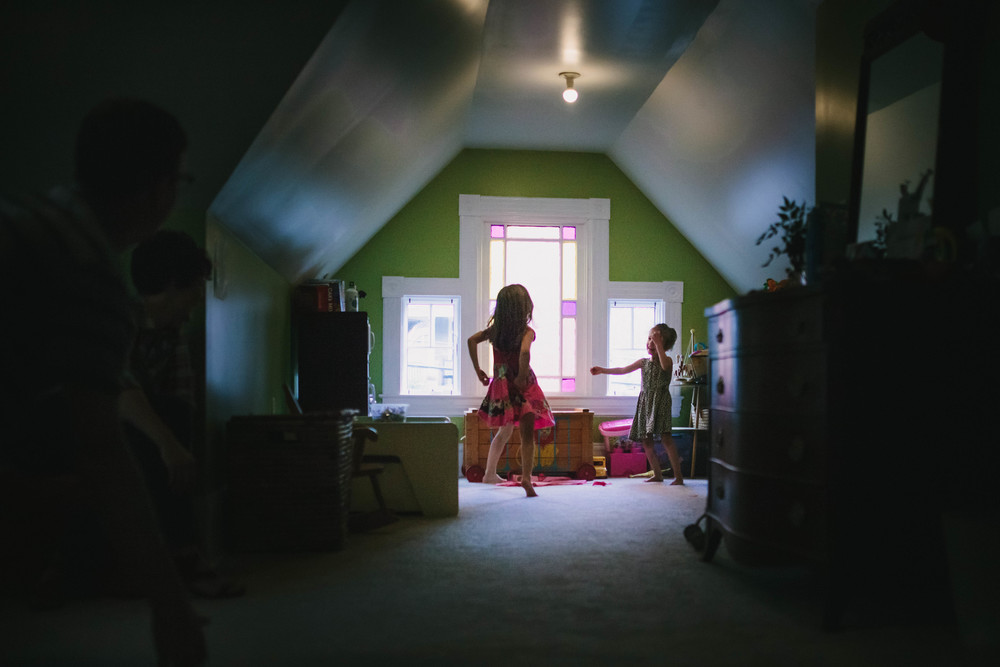 Two girls play while parents watch