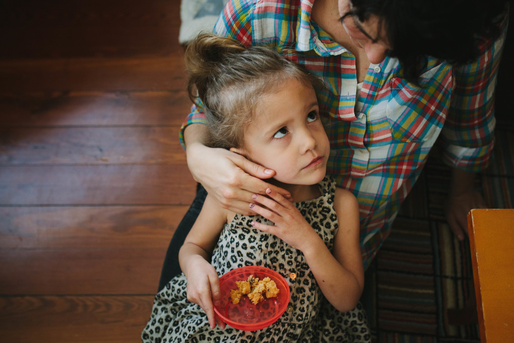 Image from family documentary session of girl in mother's lap looking up at her