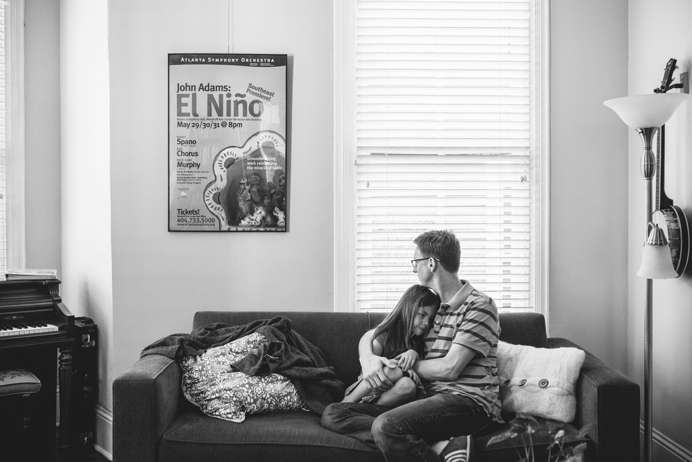 Image from family documentary session of father holding daughter on couch