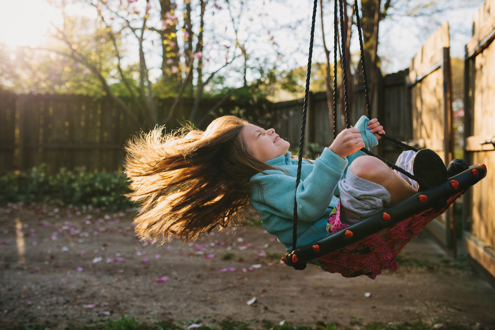 Image from family documentary session of girl on swing with hair flying behind her