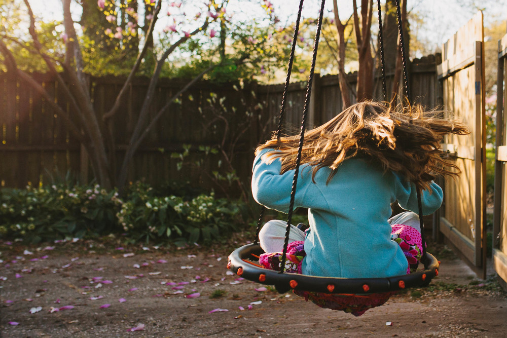 Image from family documentary session of girl spinning on swing