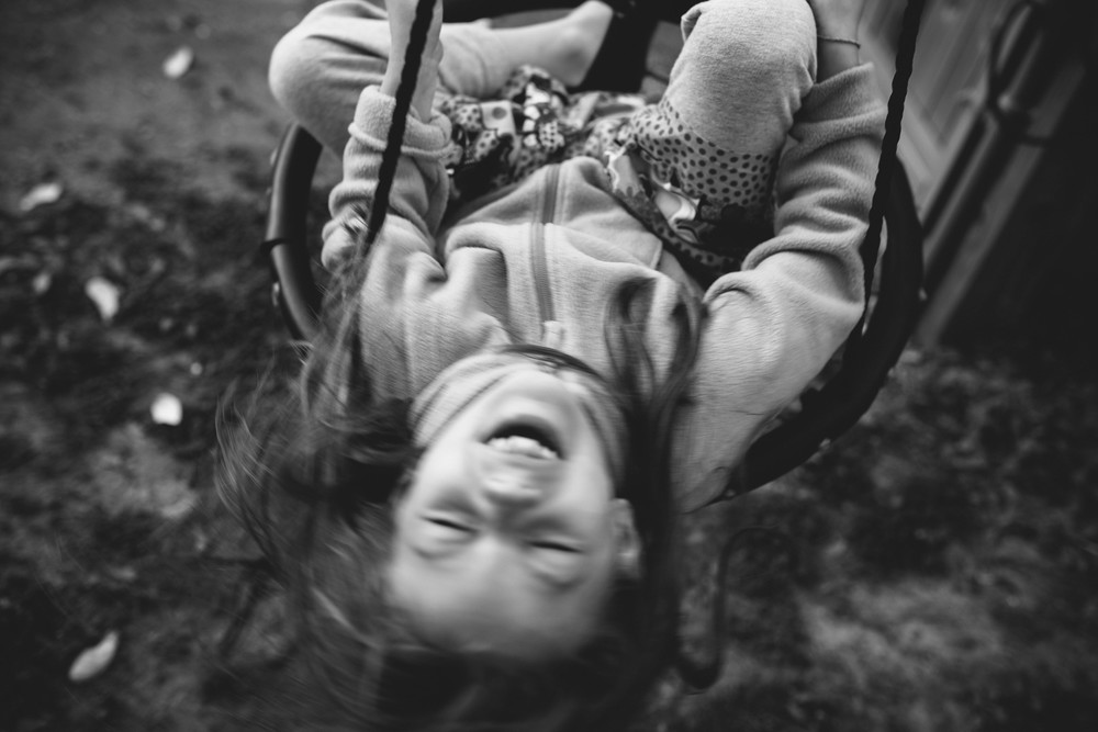 Image from family documentary session of girl smiling while spinning on swing