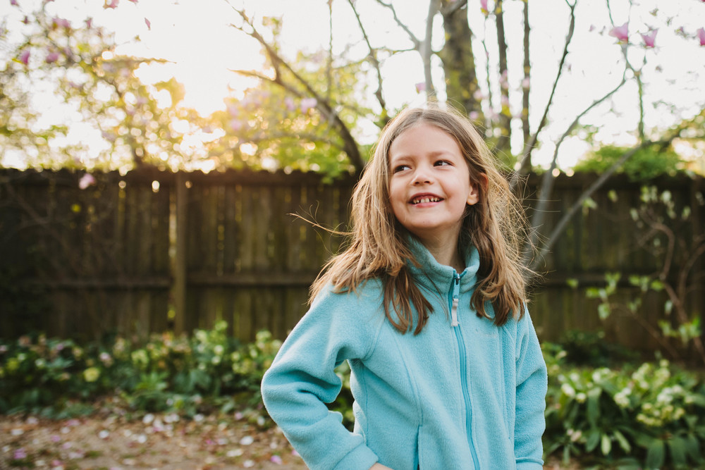 Image from family documentary session of girl smiling in backyard