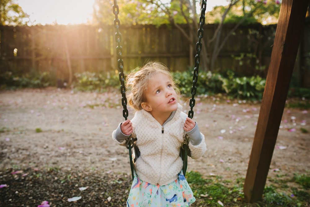 Image from family documentary session of girl looking up while on a swing