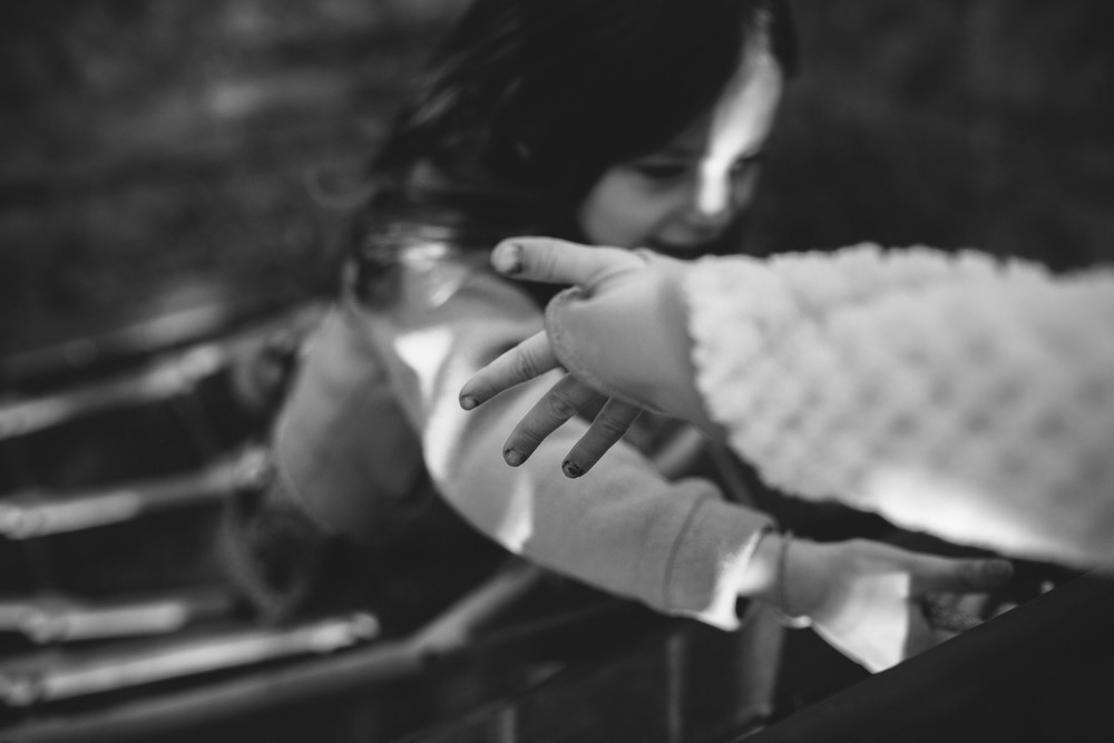 Image from family documentary session of hand reaching out to help her sister up
