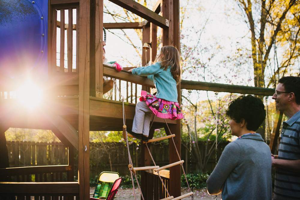 Image from family documentary session of mother and father watching children play on play structure