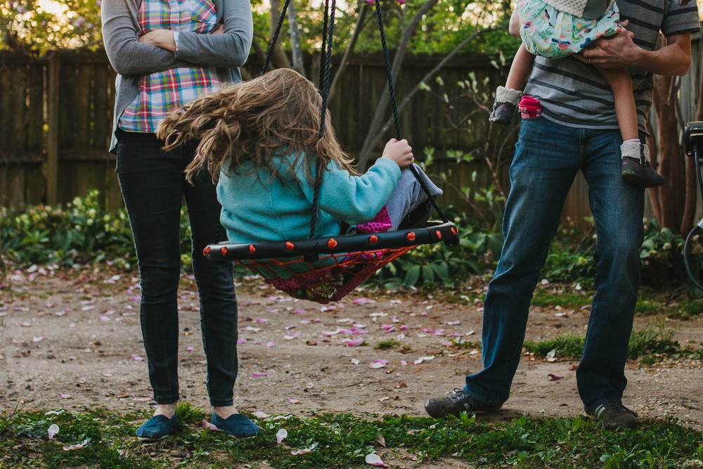 Image from family documentary session of family watching child swing