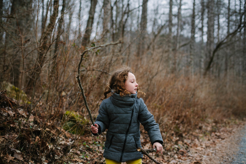 Image of girl waving stick in forest