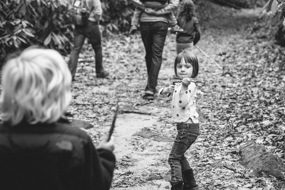 Girl with stick pretending to shoot something behind her on a path