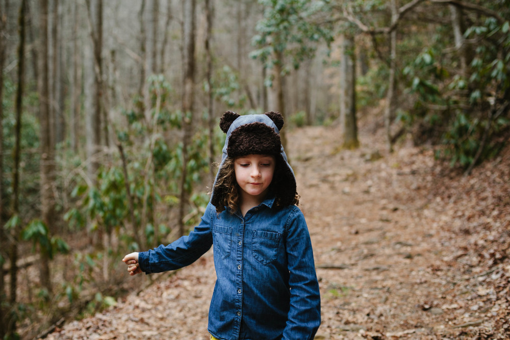 Image of girl in bear hat on path in forest