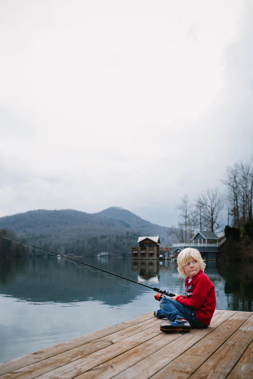 Image of boy sitting on dock fishing