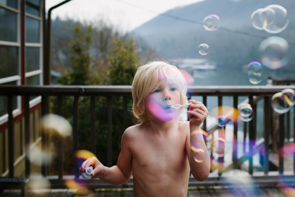 Image of boy blowing bubbles on a deck