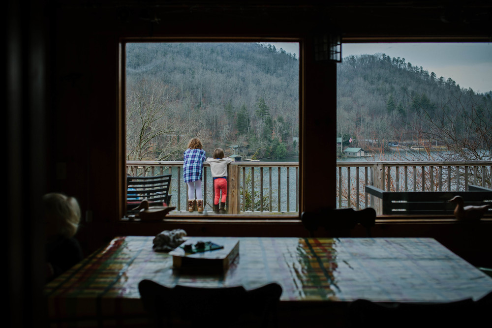 Image from the inside to two girls outside looking over deck at lake