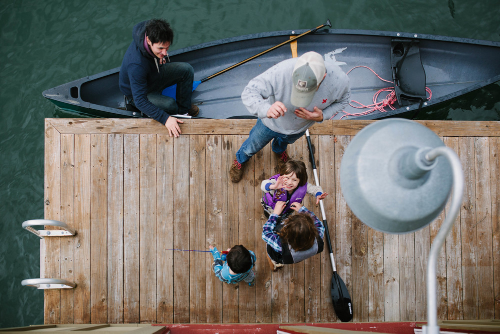 Image from above of girl waving at camera before getting on canoe