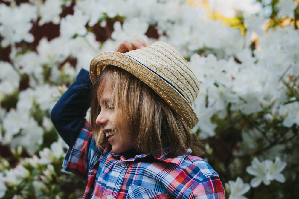 Image of boy holding hat and smiling in front of an azalea bush
