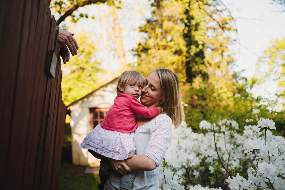 image of mother holding daughter by a fence