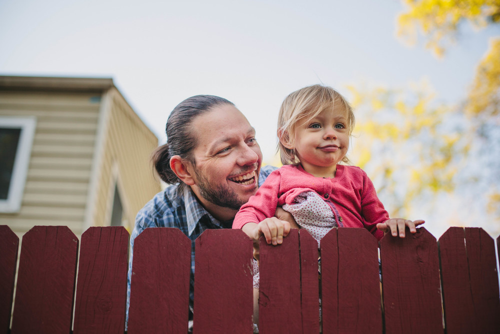 family documentary image of father holding daughter up to see over a fence