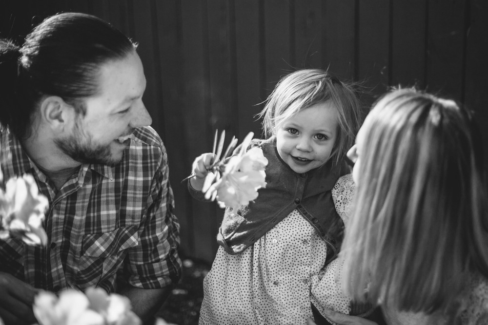 Image from family documentary session of girl holding flowers and looking at camera while her parents look at her