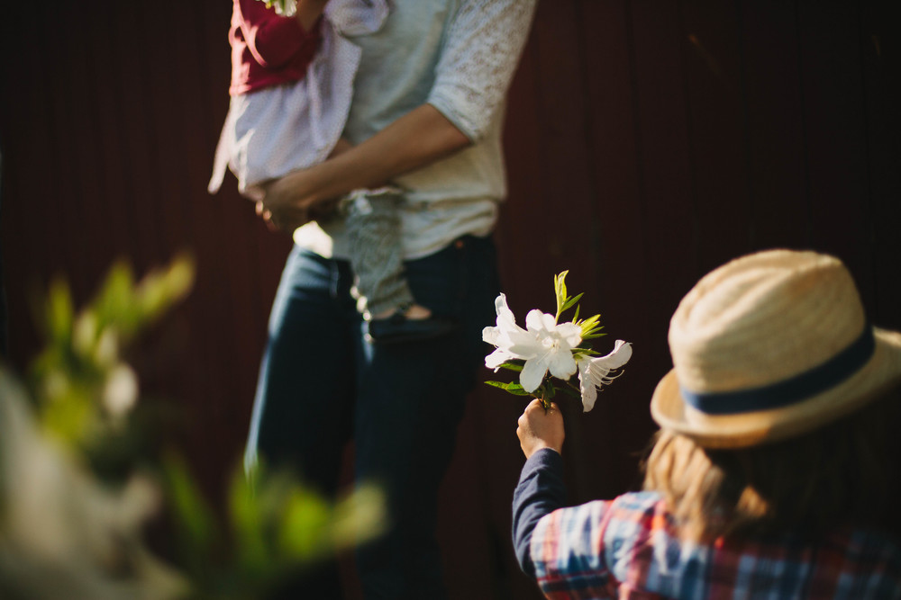 Image from family documentary session of boy presenting flowers to mother