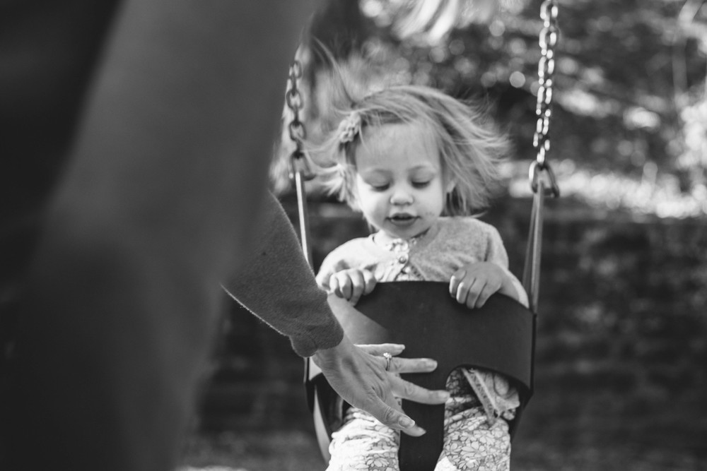 Image from family documentary session of mother pushing daughter on a swing