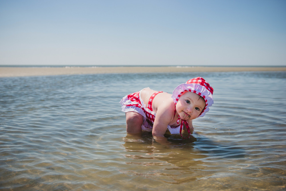 Infant in tide pool with sand on face looking at camera