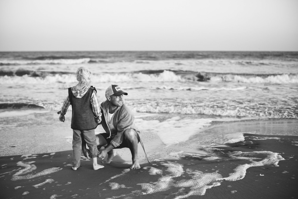 Image of father rolling up son's pants at the beach