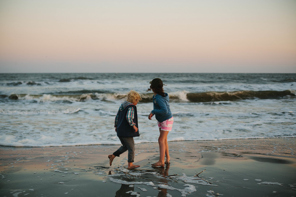 Image of a boy and a girl playing by the beach