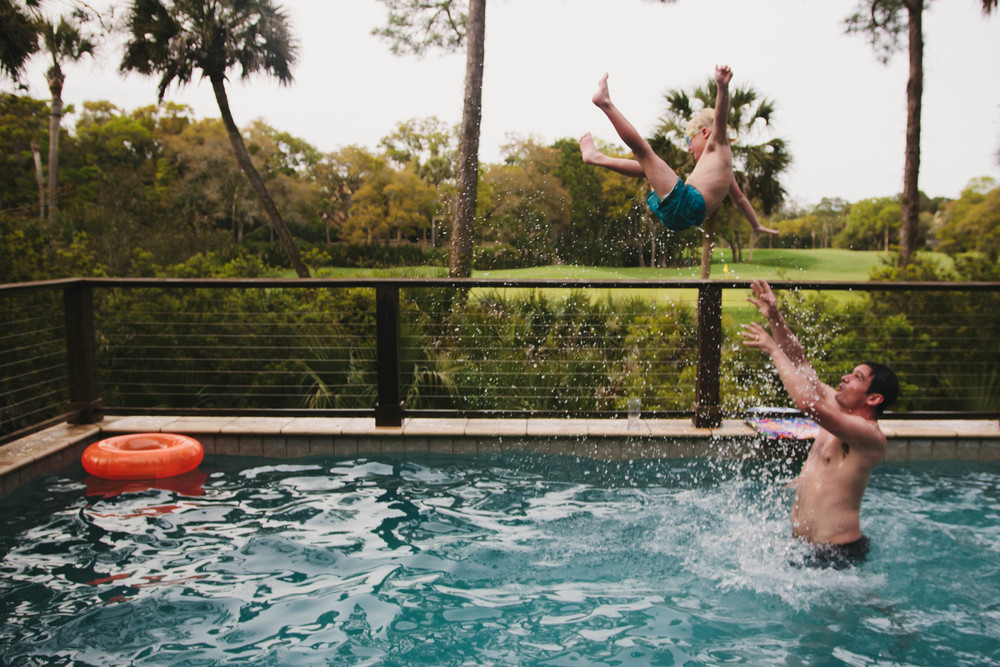 Image of boy being thrown up in the pool