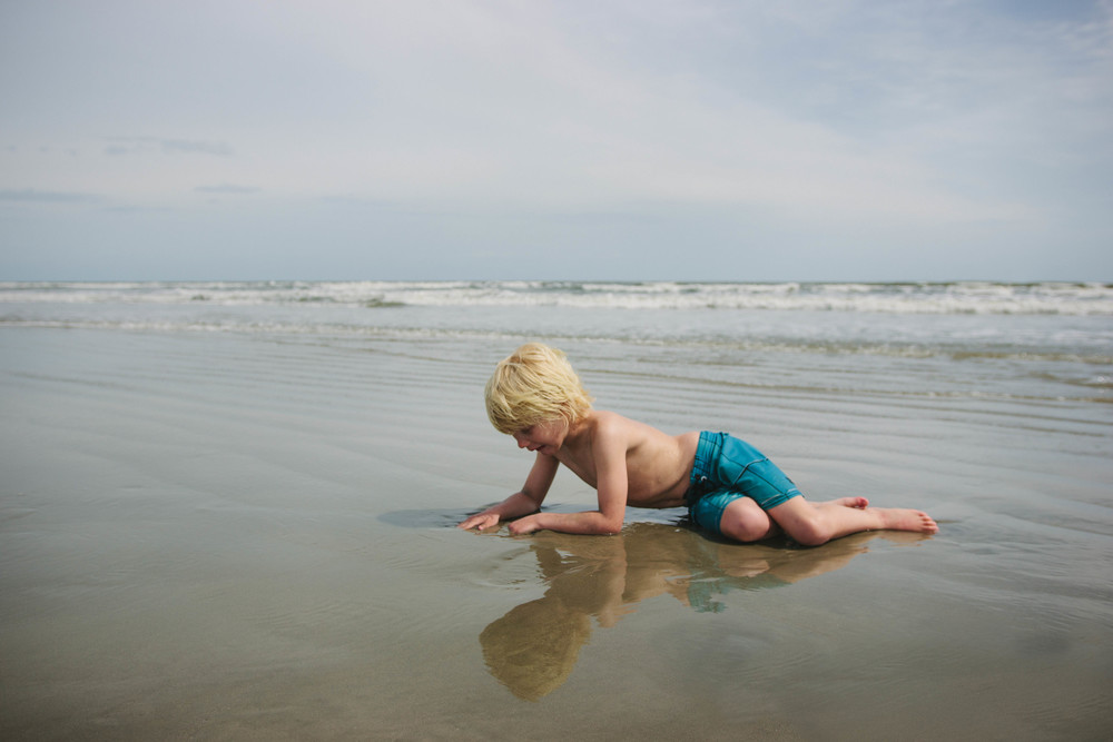 Image of boy laying down on the beach playing in the sand