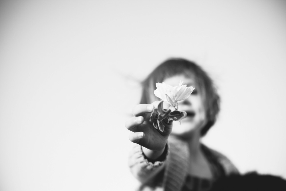Image of girl handing a flower to the photographer