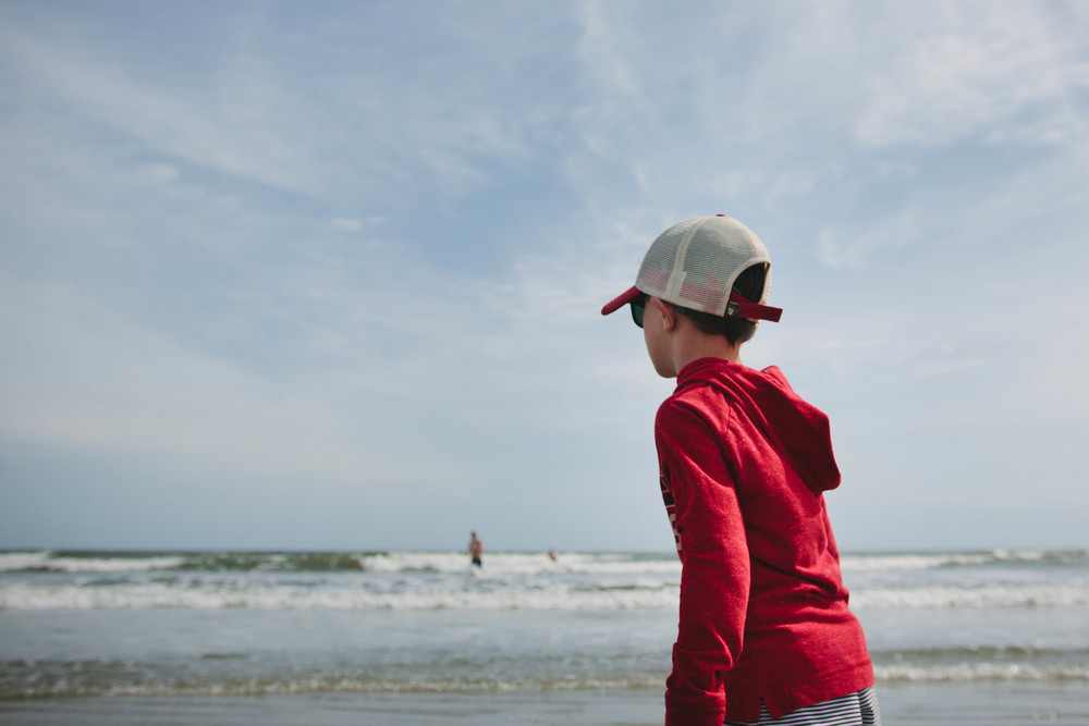 Image of a boy in a baseball cap looking out at the ocean