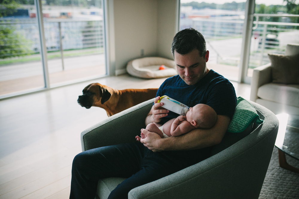 image of father giving baby a bottle with dog nearby from at home newborn documentary photography session