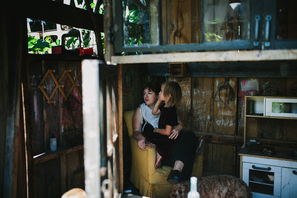 image from family documentary session of mother holding daughter in a chair in a playhouse