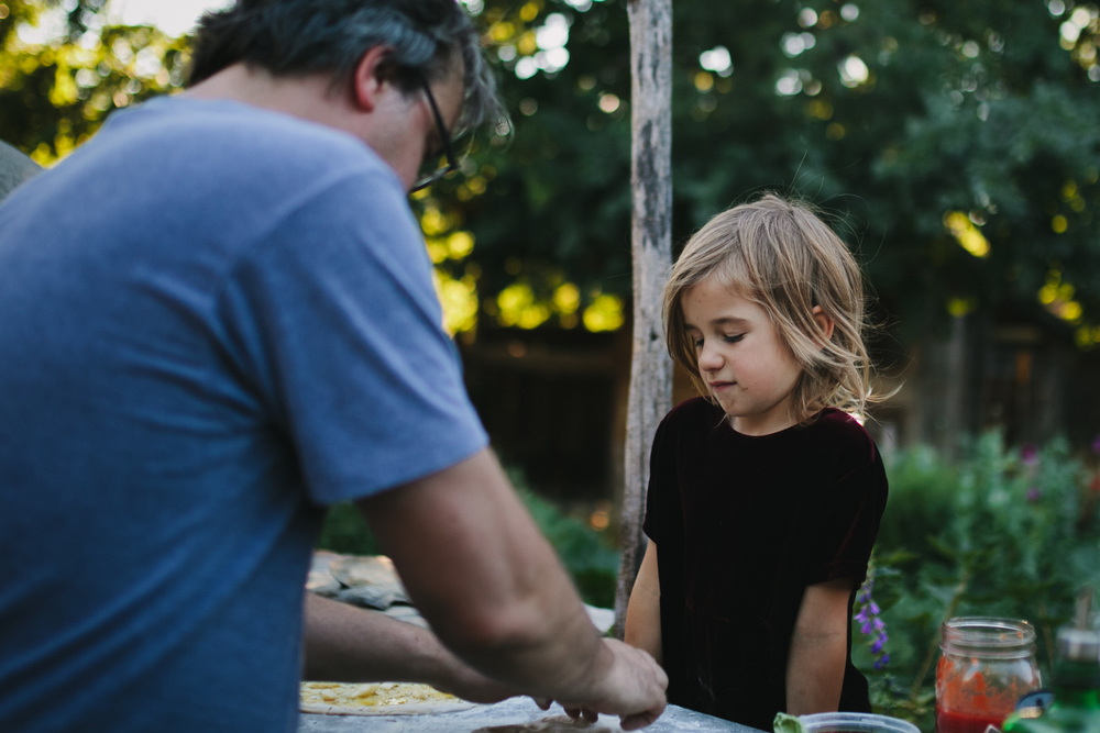 image from family documentary session of daughter looking down on father making pizza