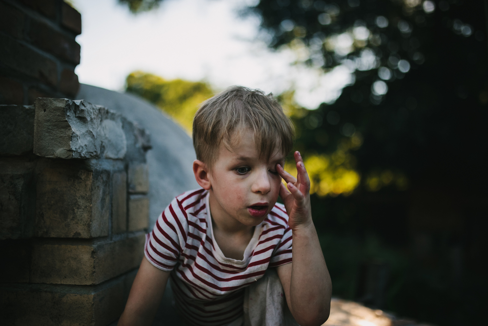 image from family documentary session of boy putting his finger on his eye
