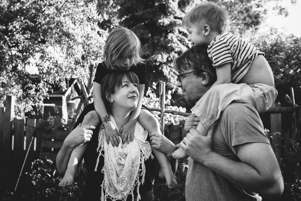 image from family documentary session of parents holding their kids on their shoulders