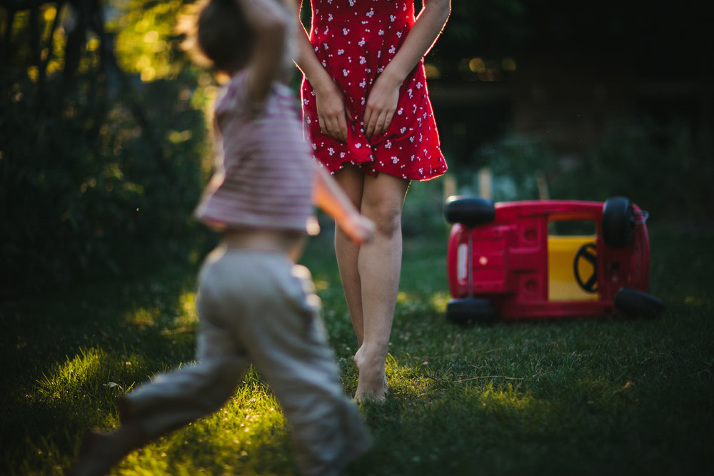 girl in red dress dancing with younger brother running in front of her from portrait of play family documentary photography session