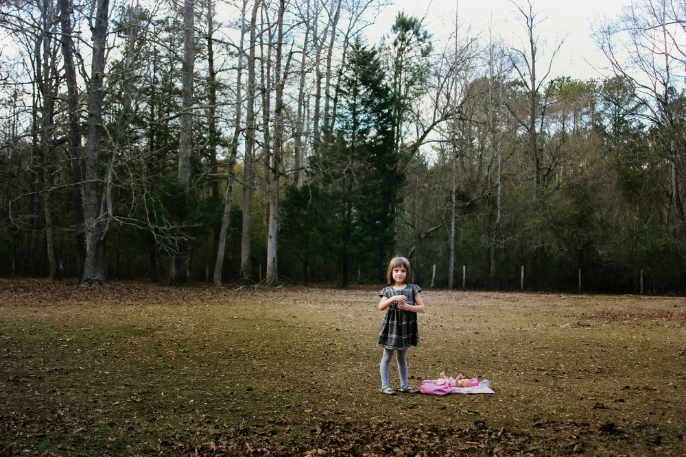 girl standing in a pasture holding a baby doll with trees behind her.