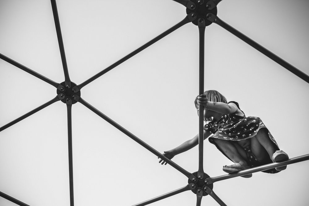 black and white image of a girl climbing on a jungle gym taken from underneath