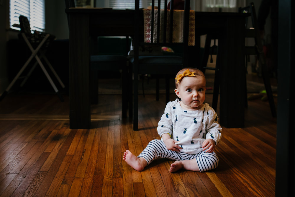baby sitting on the floor looking at camera from family documentary photography session in atlanta